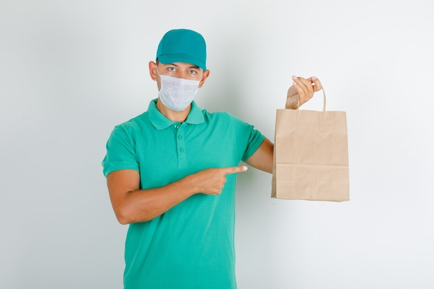 Delivery man pointing paper bag with finger in green t-shirt with cap