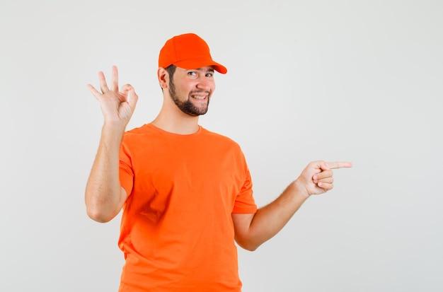Uomo di consegna che indica il lato, che mostra il segno giusto in maglietta arancione, berretto e sembra allegro. vista frontale.