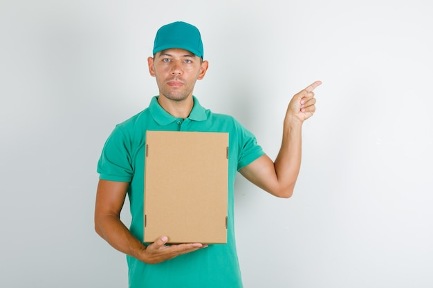 Delivery man pointing something with cardboard box in green t-shirt with cap