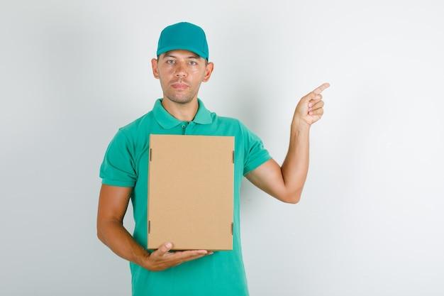 Доставщик, указывая что-то с картонной коробкой в зеленой футболке с кепкой