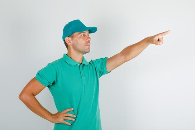 Uomo di consegna che indica qualcosa con la mano sulla vita in maglietta verde con cappuccio