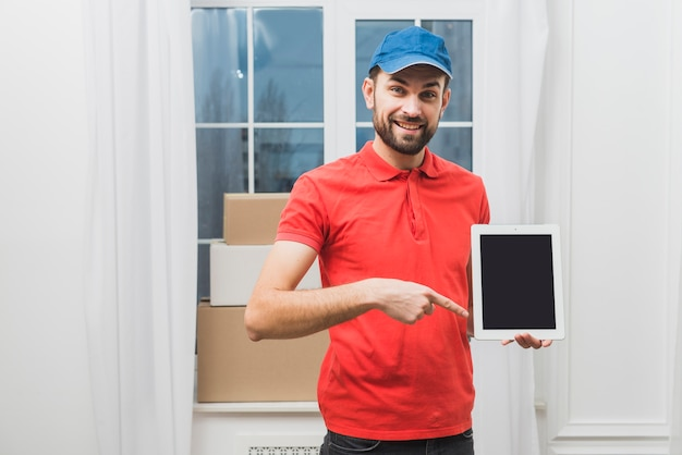 Delivery man pointing at tablet