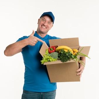 Доставка человек, указывая на продуктовый ящик
