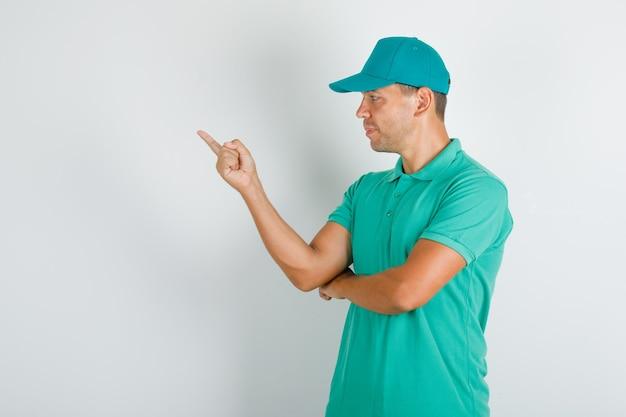 キャップ付きの緑のtシャツの側を指している配達人