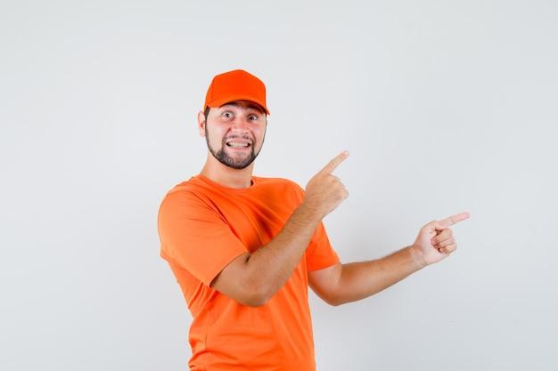 주황색 티셔츠, 모자를 쓰고 쾌활한 표정으로 옆을 가리키는 배달원. 전면보기.