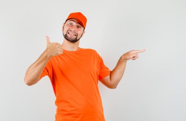 주황색 티셔츠, 모자를 쓰고 쾌활한 표정을 하고 엄지손가락으로 옆을 가리키는 배달원. 전면보기.