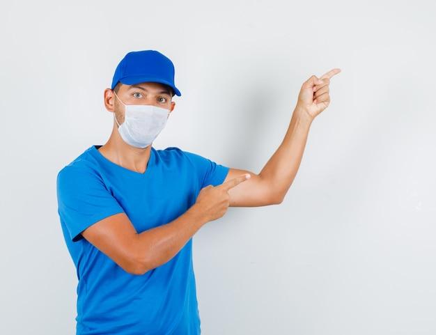 Uomo di consegna rivolto verso l'alto le dita in maglietta blu