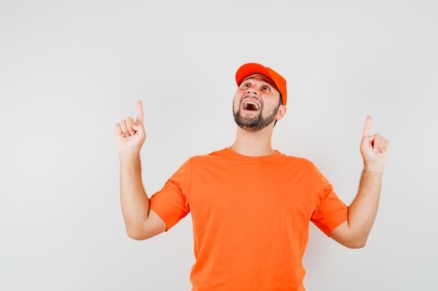 주황색 티셔츠, 모자를 쓰고 희망적으로 보이는 배달원. 전면보기.