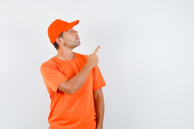 Delivery man pointing up while looking upward in orange t-shirt and cap and looking focused