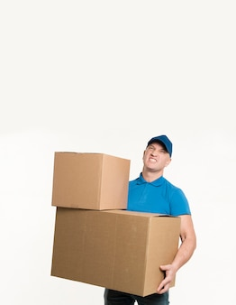 Delivery man posing while holding heavy cardboard boxes