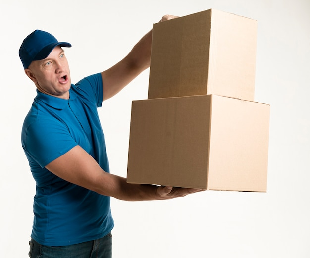 Delivery man posing with cardboard boxes in hands