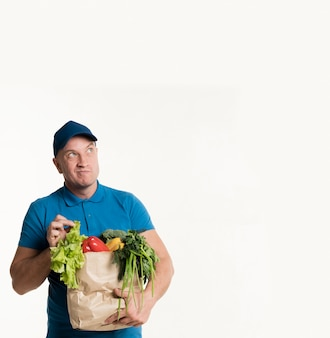 Delivery man posing with grocery bag