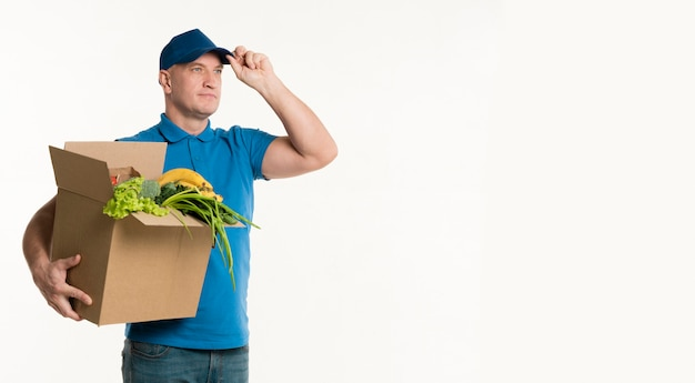 Delivery man posing with grocery box and copy space