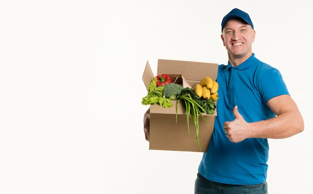 Delivery man posing with grocery box and thumbs up