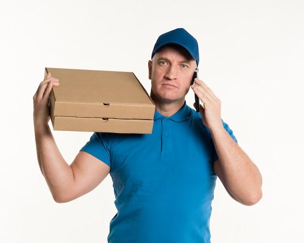 Доставка человек позирует с коробками телефона и пиццы