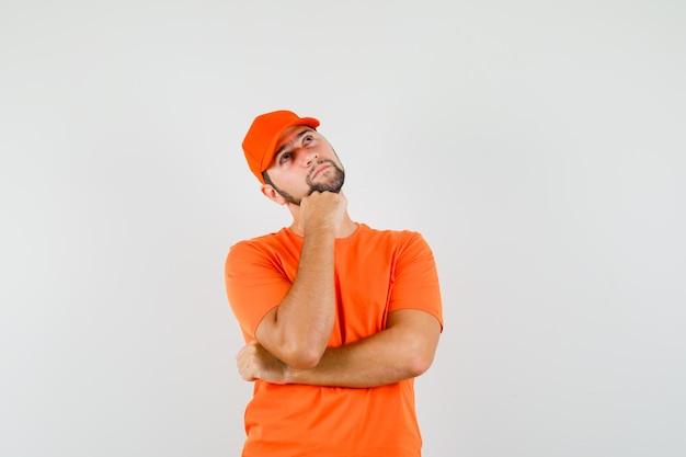 배달원은 주황색 티셔츠, 모자를 쓴 주먹에 턱을 대고 수심에 찬 앞모습을 보고 있습니다.