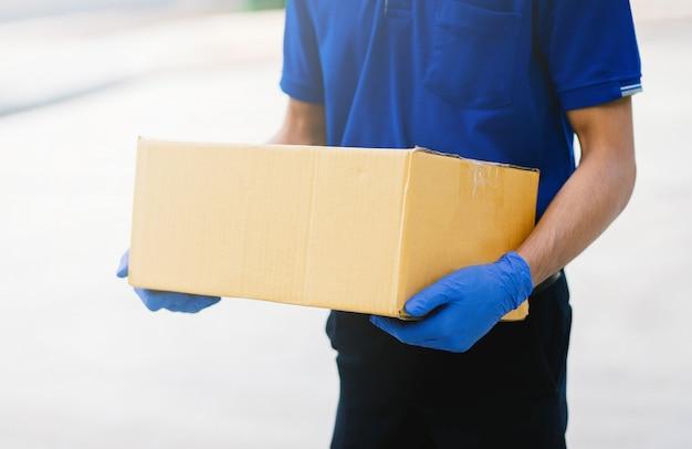 Доставщик надевает перчатки и маски для хранения картонных коробок
