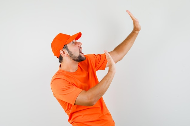 Delivery man raising hands to defend himself in orange t-shirt, cap and looking scared , front view.