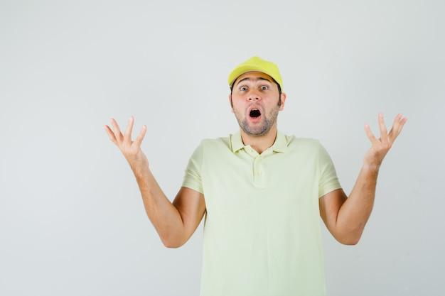 黄色い制服、正面図で困惑したジェスチャーで手を上げる配達人。