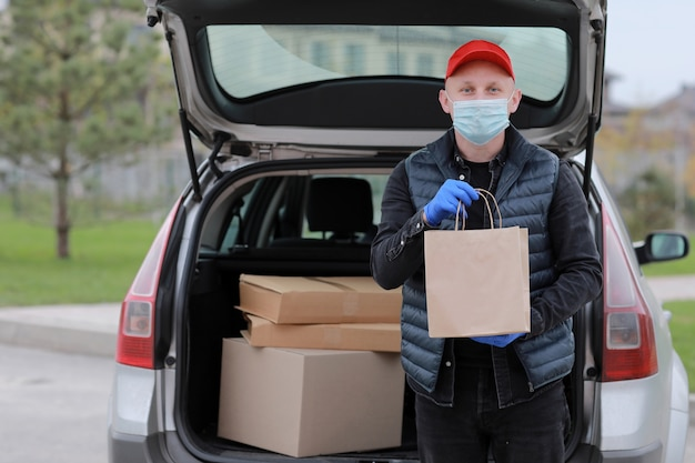 Delivery man in red cap, face medical mask and gloves hold paper bag near the car outdoor
