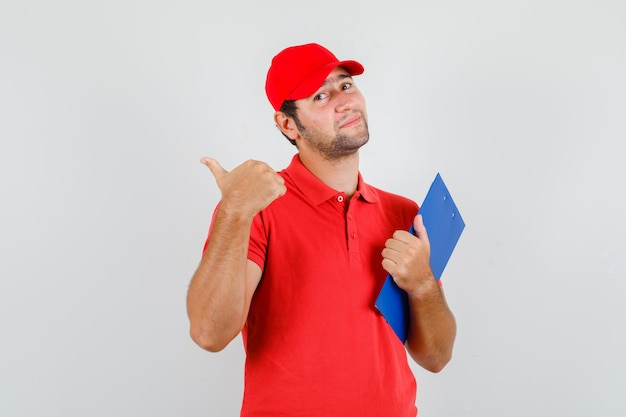 Delivery man in red t-shirt, cap holding clipboard and showing thumb up