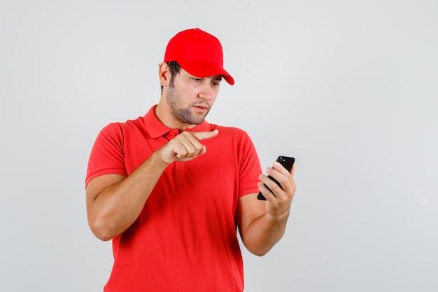 Fattorino in maglietta rossa, cappuccio guardando smartphone con segno di dito