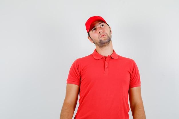 Fattorino in maglietta rossa, berretto alzando lo sguardo e guardando pensieroso