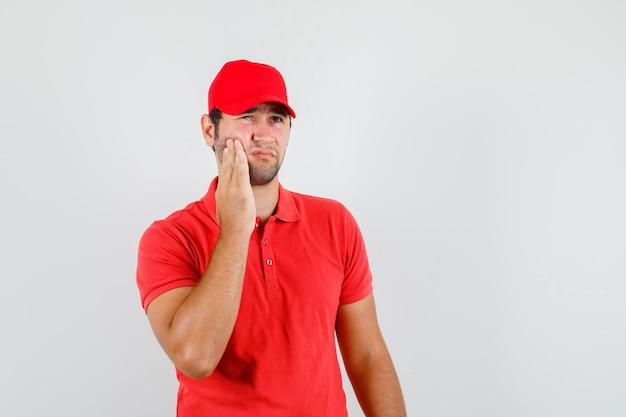 Uomo di consegna in maglietta rossa, cappuccio che soffre di mal di denti