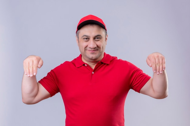 Delivery man in red uniform and cap gesturing with hand smiling  body language concept standing