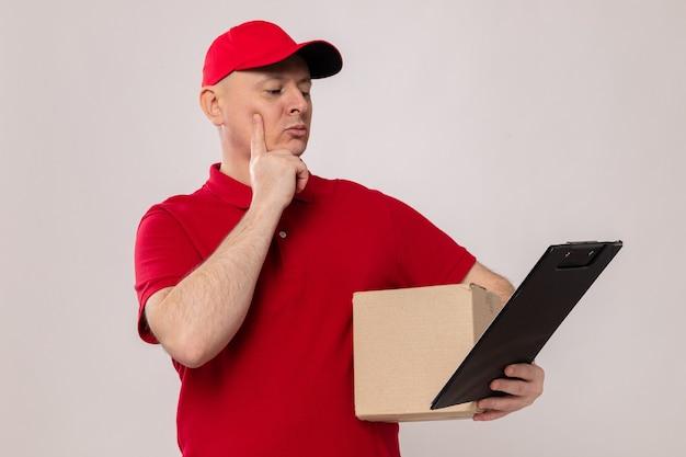 Fattorino in uniforme rossa e cappuccio con scatola di cartone e appunti guardandolo con espressione pensierosa in piedi su sfondo bianco