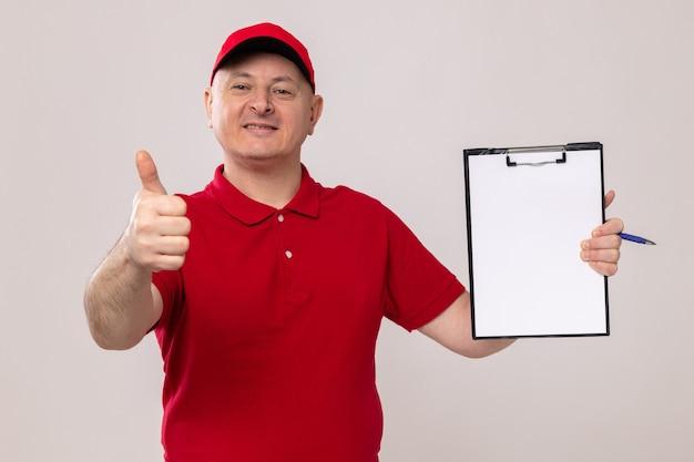 Fattorino in uniforme rossa e berretto che tiene appunti con pagine bianche che guardano la telecamera sorridendo fiducioso che mostra i pollici in su in piedi su sfondo bianco