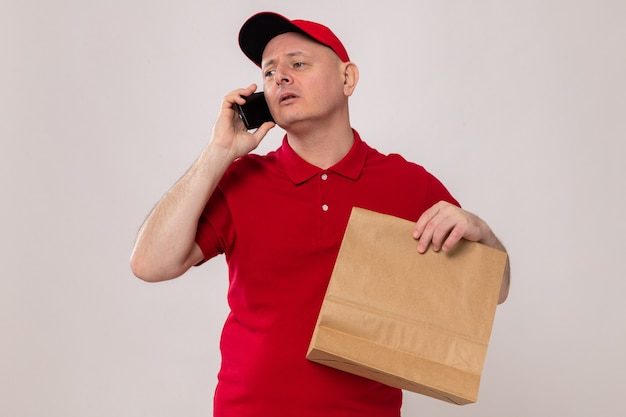 Delivery man in red uniform and cap holding paper package looking confident while talking on mobile phone standing over white background