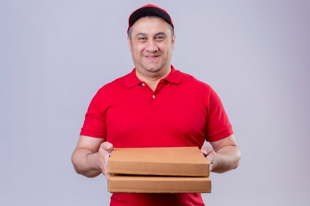 Delivery man in red uniform and cap holding pizza boxes looking positive and happy smiling friendly standing over isolated white space