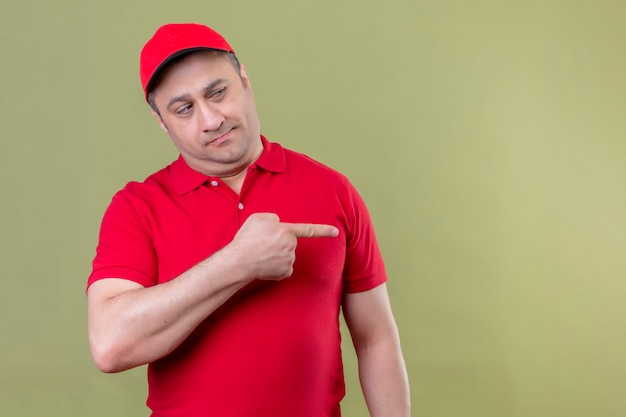 Delivery man in red uniform and cap looking aside with skeptical expression pointing with index finger to the side standing on isolated green