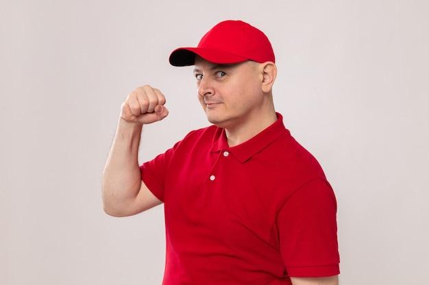 Fattorino in uniforme rossa e berretto che guarda la telecamera con espressione fiduciosa alzando il pugno come un vincitore in piedi su sfondo bianco