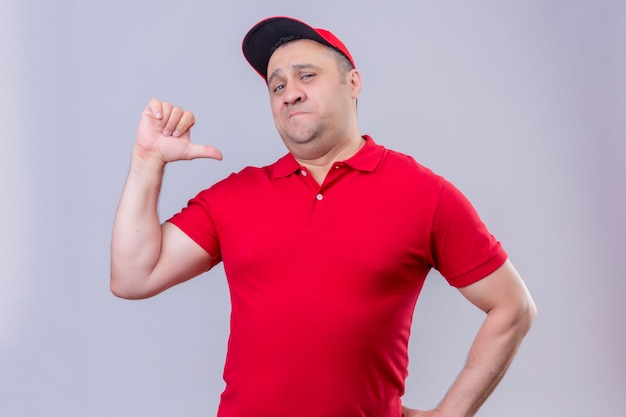 Delivery man in red uniform and cap looking confident pointing with thumb to himself proud self-satisfied standing over isolated white space Free Photo