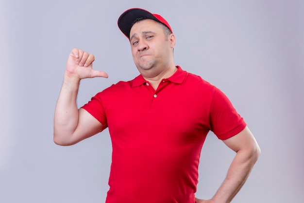 Delivery man in red uniform and cap looking confident pointing with thumb to himself proud, self-satisfied standing on isolated white