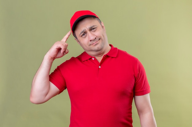 Delivery man in red uniform and cap pointing temple with finger concentrating hard on an idea standing over green space