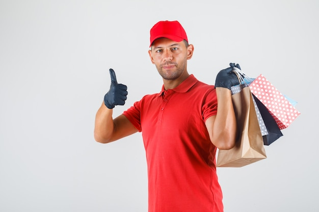 Delivery man in red uniform, gloves holding paper bags and showing thumb up and looking pleased