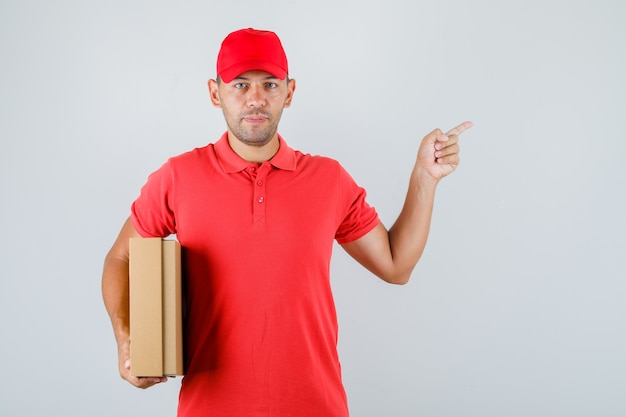 Delivery man in red uniform holding cardboard box and pointing away