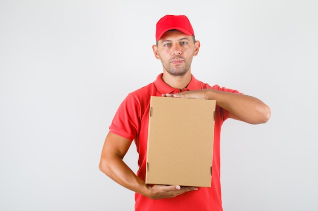 Delivery man in red uniform holding cardboard box