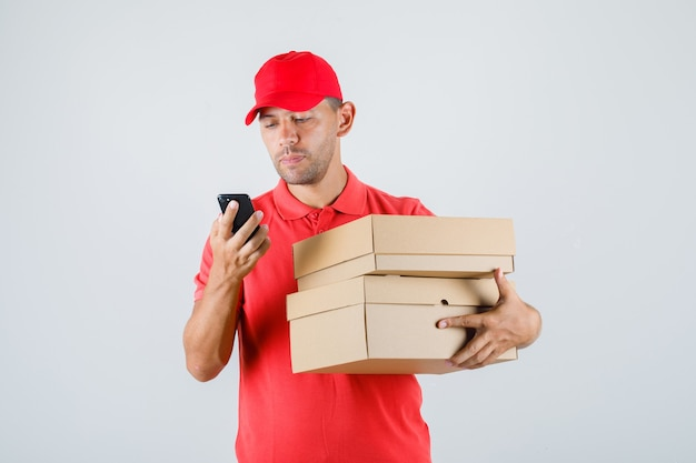 Delivery man in red uniform holding cardboard boxes while using smartphone
