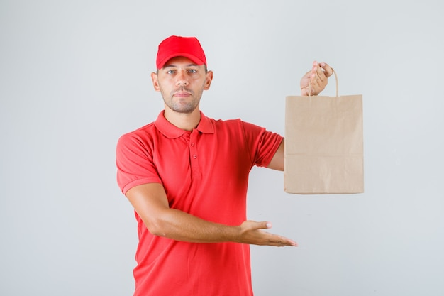 Delivery man in red uniform holding paper bag