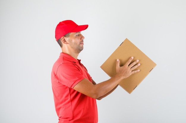 Delivery man in red uniform holding pizza box .