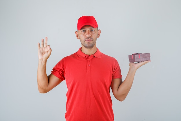 Delivery man in red uniform holding present box and showing ok sign
