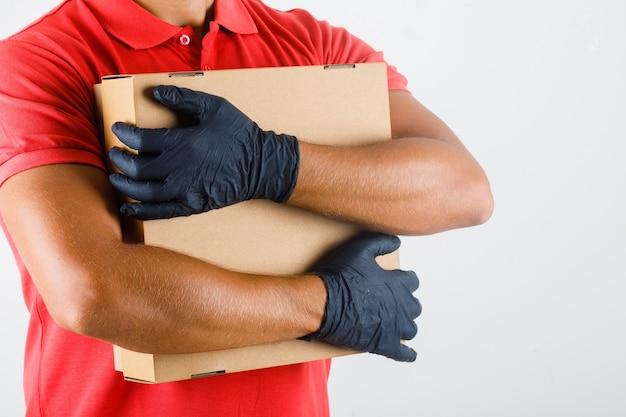 Fattorino in uniforme rossa, guanti medicali che abbraccia la scatola di cartone e che sembra fiducioso