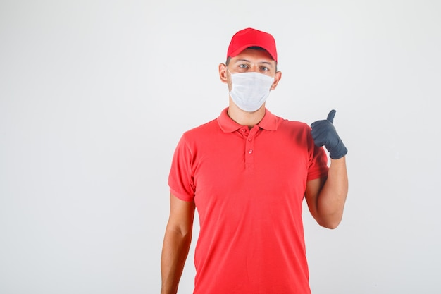 Delivery man in red uniform, medical mask, gloves showing something with finger