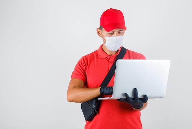 Fattorino in uniforme rossa, mascherina medica, guanti che digitano sul computer portatile