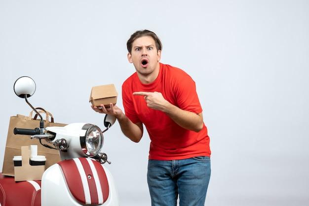 Fattorino in uniforme rossa in piedi vicino a scooter che mostra piccola scatola su sfondo bianco