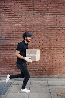 Delivery man running with parcel in front of brickwall